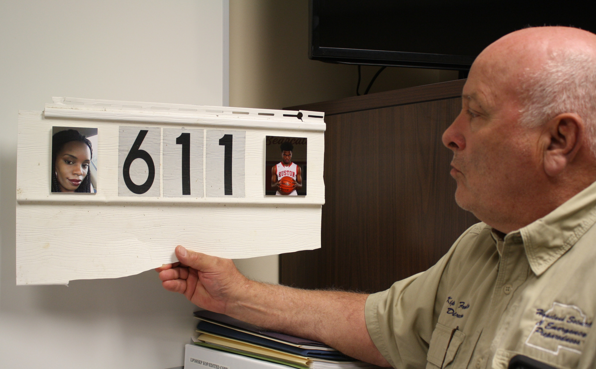 """<span style=""""font-size:12pt""""><span style=""""font-family:&quot;Times New Roman&quot;"""">Lincoln Parish Director of Homeland Security and Emergency Preparedness Kip Franklin holds a piece of siding from the Evans Street house where Kendra and Remington Butler lost their lives during the tornado. It hangs in Franklin's office with pictures of the Butlers affixed to it.</span></span>"""