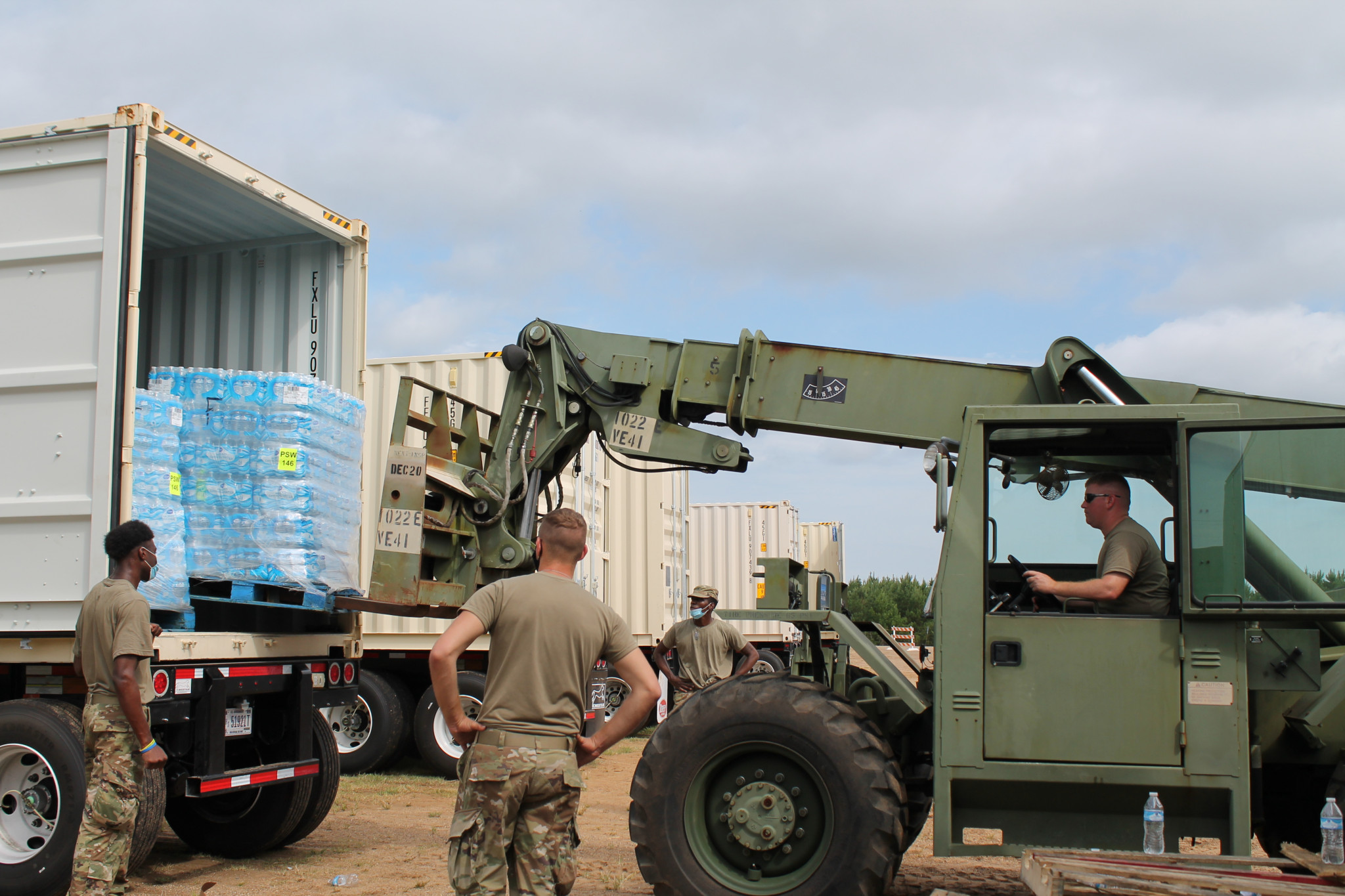 National Guardsmen use military equipment at the North Louisiana Exhibition Center Sunday to remove pallets of water brought in for parish residents