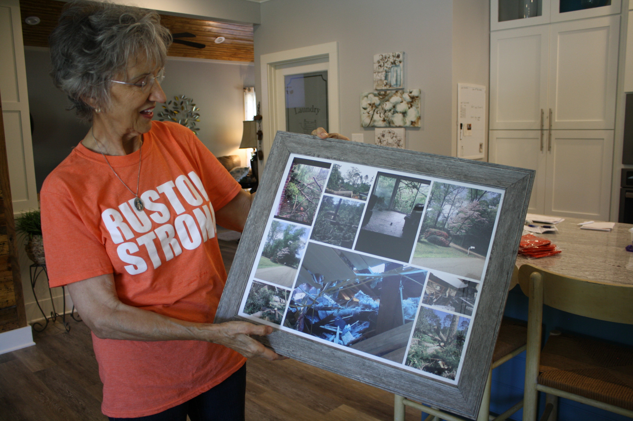 While standing in her remodeled Robinette Drive home, Mary Vidrine displays a collage of photos showing the damage the house sustained last year.