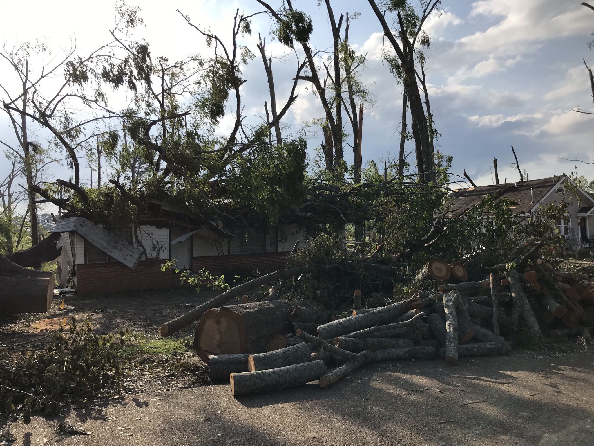 The Evans Street home of Kendra Butler, where she and her son Remington lost thier lives the night of the tornado, is pictured here soon afterward with piles of tree debris stacked on top of it.