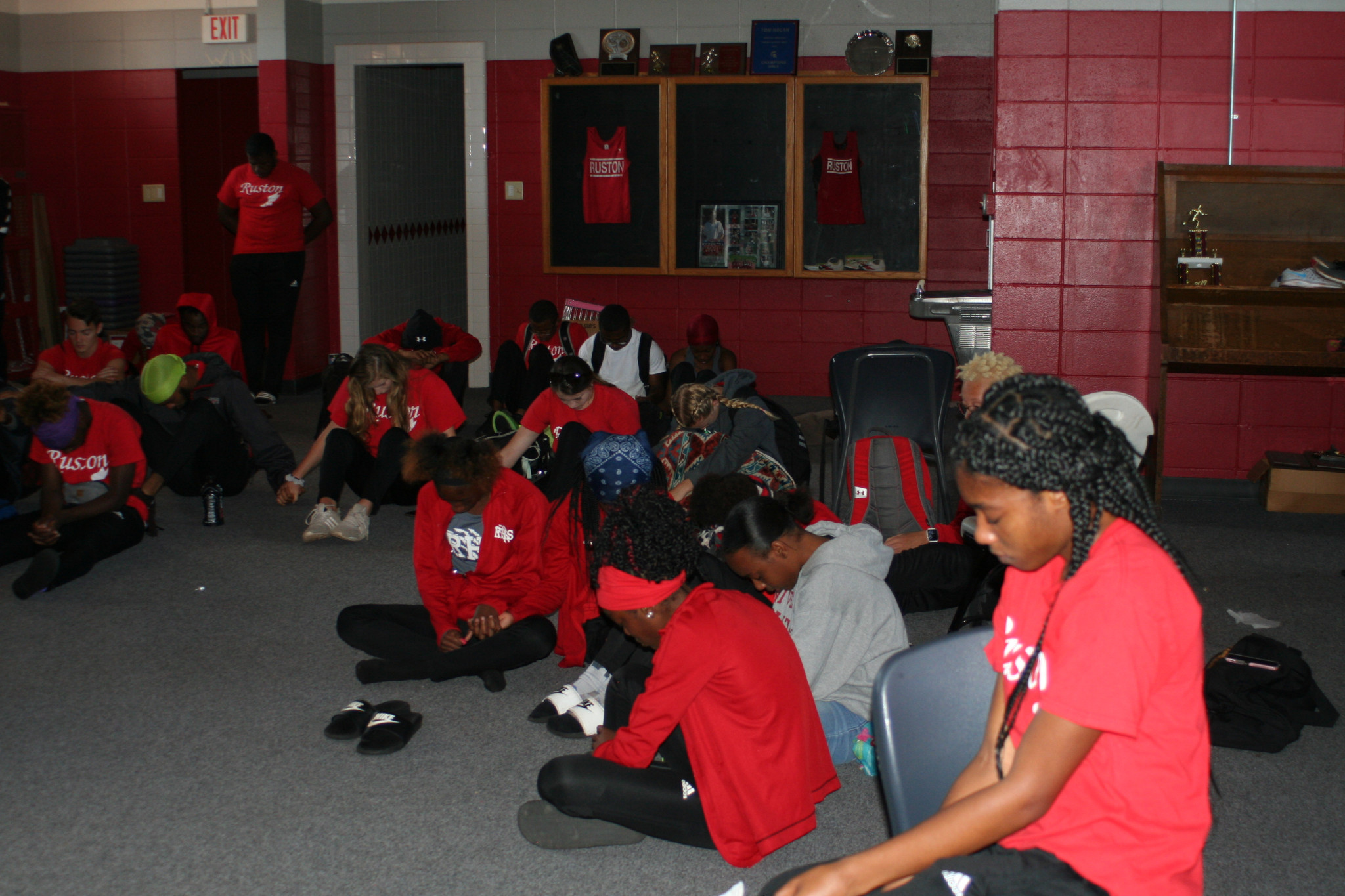 The Ruston High School track and field team praying for teammate Cam Murphy, who lost his mother and brother in the tornado, before leaving for the regional track meet — April 26